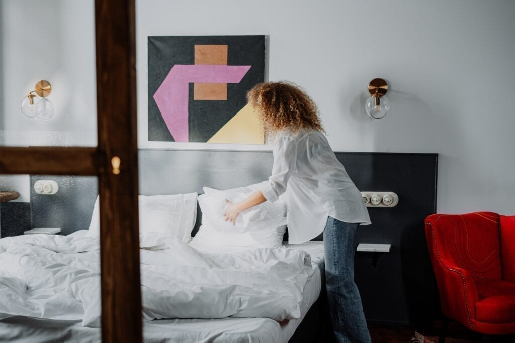 Woman protecting bed, mattress, and sheets from bed bugs